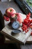 Reloj, libros y manzana en el travesaño viejo de la ventana Imagen de archivo libre de regalías