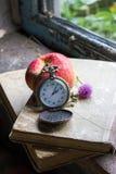 Reloj, libros y manzana en el travesaño viejo de la ventana Fotos de archivo libres de regalías