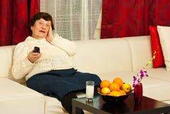 Reloj mayor TV de la mujer en sala de estar Foto de archivo