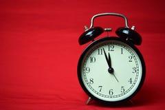 Reloj que hace tictac a las 12 en el fondo rojo fotografía de archivo