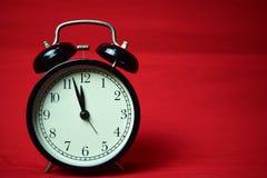 Reloj que hace tictac a las 12 en el fondo rojo imagenes de archivo