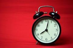 Reloj que hace tictac a las 8 en el fondo rojo fotos de archivo libres de regalías