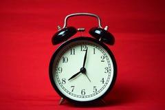 Reloj que hace tictac a las 8 en el fondo rojo foto de archivo libre de regalías