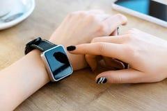 Reloj que lleva de la muchacha, taza de café en la tabla Fotografía de archivo libre de regalías