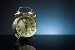 Reloj retro, cinco a doce, fondo azul Imagen de archivo libre de regalías