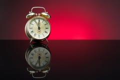 Reloj retro, cinco a doce, fondo rojo Fotografía de archivo libre de regalías