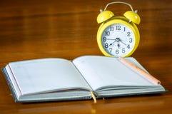 Reloj retro del alarrm con el libro Imagenes de archivo