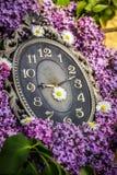 Reloj rodeado por las flores de la primavera Profundidad del campo baja con el foco selectivo en el reloj Flores de la lila Fotografía de archivo