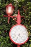 Reloj rojo antiguo en el jardín Imagen de archivo libre de regalías