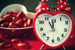 Reloj rojo del amor de la forma del corazón y chocolated Imagenes de archivo