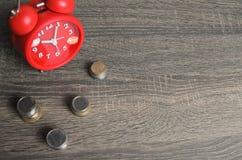 Reloj rojo del viejo estilo con un poco de dinero alrededor Foto de archivo