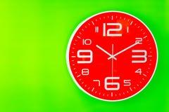 Reloj rojo en fondo verde de la pared Imagen de archivo libre de regalías