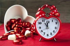 Reloj rojo en forma de corazón del amor de la tarjeta del día de San Valentín con chocola Imágenes de archivo libres de regalías