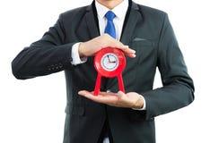 Reloj rojo que se sostiene en manos del hombre de negocios aislado fotos de archivo