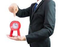 Reloj rojo que se sostiene en manos del hombre de negocios aislado foto de archivo