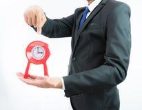 Reloj rojo que se sostiene en manos del hombre de negocios aislado fotos de archivo libres de regalías