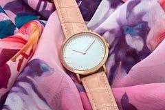 Reloj rosado en fondo colorido de la tela de seda fotografía de archivo