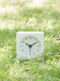 Reloj simple blanco en la yarda del césped, 10:10 diez diez Fotos de archivo libres de regalías