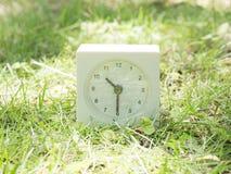 Reloj simple blanco en la yarda del césped, 10:30 diez treinta medios Imágenes de archivo libres de regalías