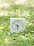 Reloj simple blanco en la yarda del césped, 10:30 diez treinta medios Imagen de archivo libre de regalías
