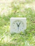 Reloj simple blanco en la yarda del césped, 11:05 once cinco Fotografía de archivo