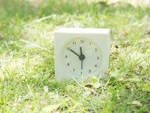 Reloj simple blanco en la yarda del césped, 11:50 once cincuenta Fotografía de archivo libre de regalías