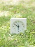 Reloj simple blanco en la yarda del césped, 11:50 once cincuenta Fotografía de archivo