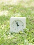 Reloj simple blanco en la yarda del césped, 11:55 once cincuenta y cinco Foto de archivo libre de regalías