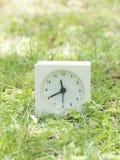 Reloj simple blanco en la yarda del césped, 11:40 once cuarenta Imágenes de archivo libres de regalías