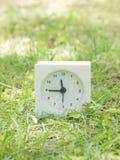 Reloj simple blanco en la yarda del césped, 11:45 once cuarenta y cinco Fotografía de archivo
