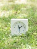 Reloj simple blanco en la yarda del césped, 11:10 once diez Imagenes de archivo