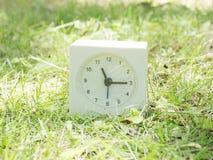 Reloj simple blanco en la yarda del césped, 11:15 once quince Fotos de archivo
