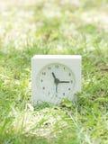 Reloj simple blanco en la yarda del césped, 11:15 once quince Fotografía de archivo libre de regalías