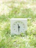 Reloj simple blanco en la yarda del césped, 11:30 once treinta medios Foto de archivo libre de regalías