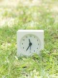 Reloj simple blanco en la yarda del césped, 11:35 once treinta y cinco Imágenes de archivo libres de regalías