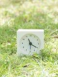 Reloj simple blanco en la yarda del césped, 11:20 once veinte Fotografía de archivo
