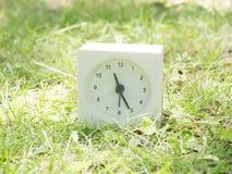 Reloj simple blanco en la yarda del césped, 11:25 once veinticinco Fotos de archivo libres de regalías