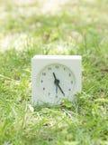 Reloj simple blanco en la yarda del césped, 11:25 once veinticinco Imágenes de archivo libres de regalías