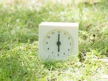 Reloj simple blanco en la yarda del césped, 6:00 seis relojes del ` de o Foto de archivo libre de regalías