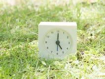 Reloj simple blanco en yarda del césped, reloj del ` del 5:00 cinco o Fotos de archivo libres de regalías