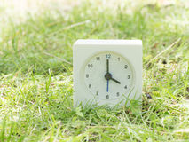 Reloj simple blanco en yarda del césped, reloj del ` del 4:00 cuatro o Foto de archivo libre de regalías