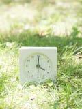 Reloj simple blanco en yarda del césped, reloj del ` del 4:00 cuatro o Fotos de archivo libres de regalías