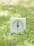 Reloj simple blanco en yarda del césped, reloj del ` del 12:00 doce o Fotografía de archivo