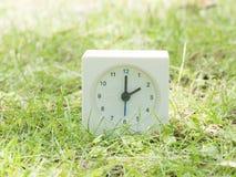 Reloj simple blanco en yarda del césped, reloj del ` del 2:00 dos o Imágenes de archivo libres de regalías