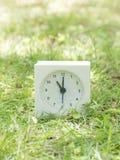 Reloj simple blanco en yarda del césped, reloj del ` del 11:00 once o Imagenes de archivo