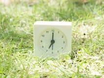 Reloj simple blanco en yarda del césped, reloj del ` del 7:00 siete o Foto de archivo