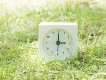 Reloj simple blanco en yarda del césped, reloj del ` del 3:00 tres o Imagen de archivo libre de regalías