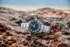 Reloj suizo costoso en una roca - Molokai, Hawaii imagenes de archivo