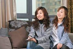 Reloj TV de dos chicas jóvenes Fotos de archivo libres de regalías
