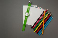 Reloj, un cuaderno y lápiz en un fondo gris imagen de archivo libre de regalías
